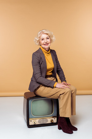 Smiling stylish senior woman sitting on vintage television Foto de archivo