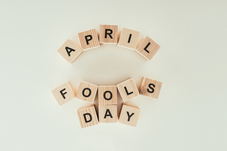 Top view of arranged wooden cubes in April fools day lettering isolated on grey tabletop, 1 April holiday concept