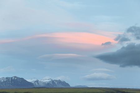 Beautiful snow-covered mountains, green grassy meadow and cloudy sky in Iceland