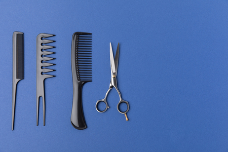 Flat lay with black hairbrushes and scissors, isolated on blue background