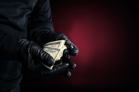 Man in black gloves holding dollar banknotes Stockfoto