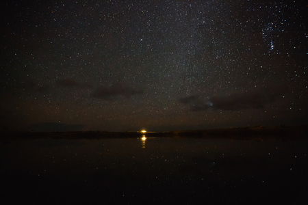 Illuminated building reflected in water and spectacular starry sky at night, Iceland