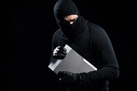Burglar in balaclava holding top secret documents Zdjęcie Seryjne