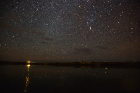 Illuminated building reflected in water and majestic starry sky at night, Iceland Banco de Imagens