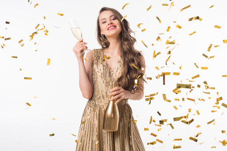 Smiling attractive woman standing with champagne under falling confetti isolated on white background