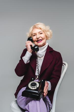 Happy senior stylish woman sitting on chair and talking on rotary phone Banco de Imagens