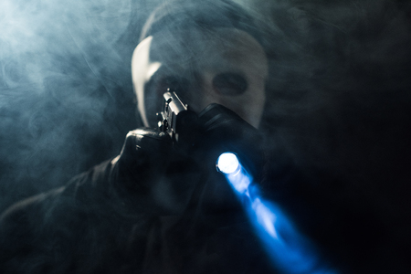 Criminal in mask and balaclava aiming with gun and flashlight
