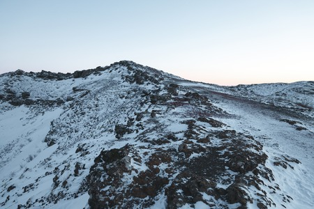 Rocky peaks with snow and sky at sunrise, Iceland