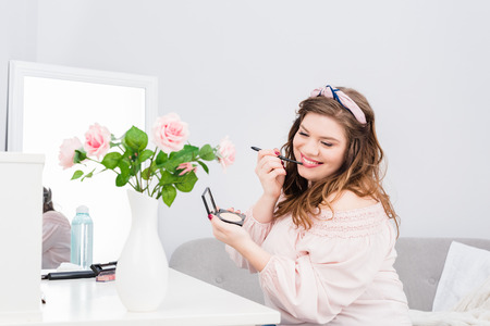 Pretty smiling young woman applying lip gloss while doing makeup at home