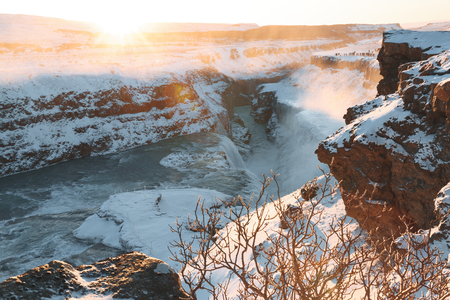 Spectacular view of beautiful Gullfoss waterfall and snow-covered rocks at sunrise, Iceland