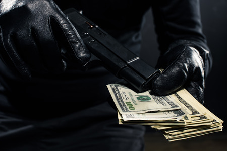 Close-up view of gun and dollars in hands of robber