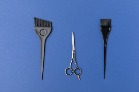 Top view of black brushes and scissors, isolated on blue background Фото со стока - 110825753