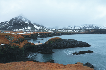 Beautiful scenic landscape with fjord and rocky mountains in snow, Iceland