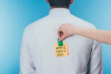 Cropped shot of woman putting note with April fools day lettering on males back, April fools day concept 免版税图像