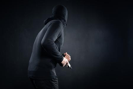 Robber with gun sneaking on black background Zdjęcie Seryjne