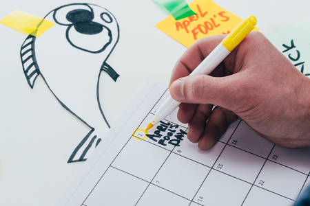 Partial view of man making note on calendar isolated on grey background, April fools day concept