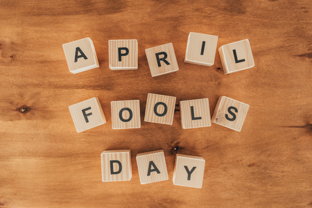 Top view of arranged wooden cubes in April fools day lettering on wooden tabletop, 1 April holiday concept Stock Photo