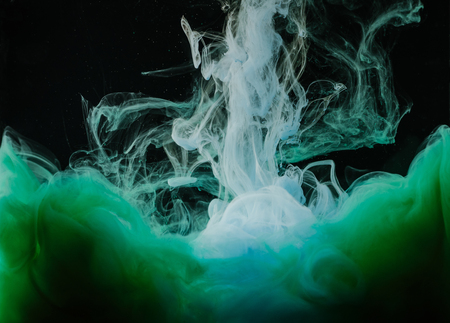 Close-up view of abstract white, green and blue ink on black background Stock Photo
