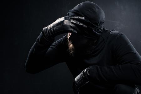 Burglar in balaclava leaning his head on hand Zdjęcie Seryjne