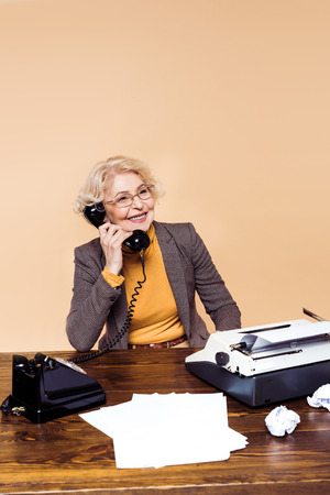 Smiling stylish senior woman in eyeglasses talking on rotary phone at table Banque d'images - 110825936