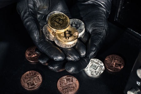 Stack of bitcoin in hands of thief wearing gloves Stock Photo