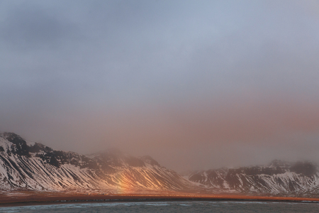 Majestic landscape with snow-covered mountains, fjord and rainbow in Iceland