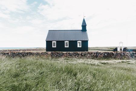 Belle petite église noire et mur de pierre avec portes à Budir, péninsule de Snaefellsnes, Islande
