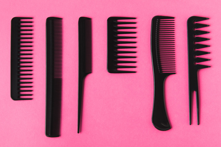 Top view of black hair combs, isolated on pink background