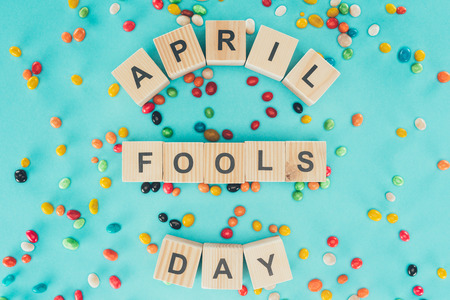 Top view of arranged wooden cubes in April fools day lettering on blue surface with candies, 1 April holiday concept