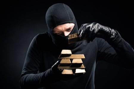 Robber in balaclava stacking gold bullions in his hands Stock Photo