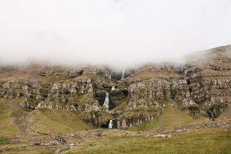 Beautiful Icelandic landscape with scenic waterfall on rocky slope in fog, Eastern Iceland Фото со стока