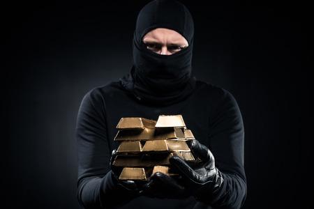 Homme en cagoule tenant des lingots d'or dans ses mains