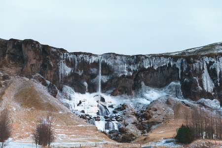 Majestic landscape with rocky mountains and frozen waterfall in Iceland
