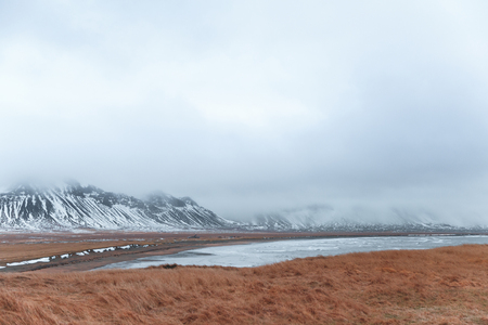 Beautiful scenic landscape with grassy meadow, fjord and snow-covered mountains, Iceland