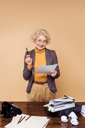 Stylish senior woman in eyeglasses looking at paper near table with typewriter and rotary phone Stock Photo