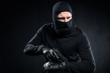 Male criminal in gloves with gun checking his watch Stock Photo