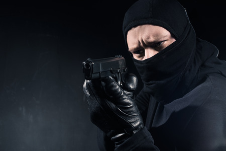 Robber in balaclava and gloves aiming with gun on black background
