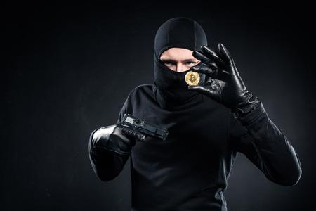 Man in black balaclava holding gun and golden bitcoin Zdjęcie Seryjne