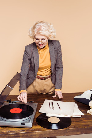Senior stylish woman turning on vinyl record player at table with typewriter and vinyl disc