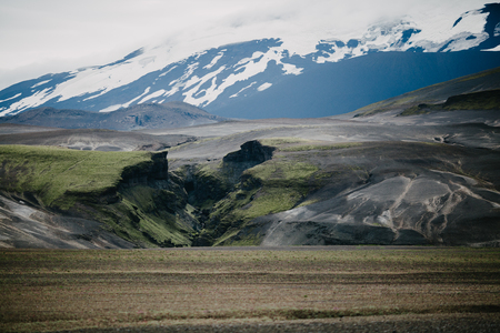 Majestic landscape with snow-covered mountains, magnificent natural formations and green vegetation in Iceland 写真素材