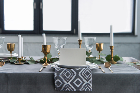 Close up view of empty card on plates on tabletop with beautiful rustic setting for guests