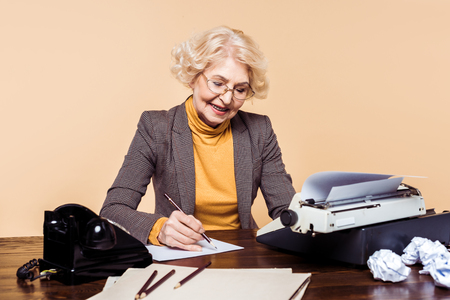 Stylish senior woman writing on paper at table with typewriter and rotary phone Reklamní fotografie - 110882365