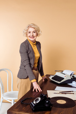 Stylish senior woman standing at table with rotary phone, vinyl plate and typewriter Stock fotó