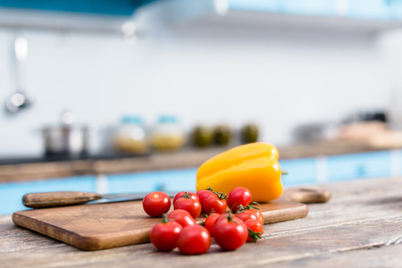 Selective focus of fresh cherry tomatoes and bell pepper on tabletop with wooden cutting board and knife Stock Photo