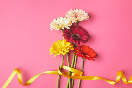 Bouquet of colorful Gerbera flowers tied with yellow ribbon, mothers day concept Banco de Imagens
