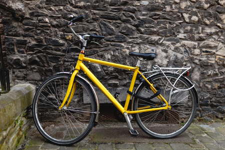 Modern yellow bicycle near old stone wall in Ghent, Belgium Stock Photo