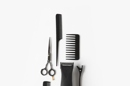 Flat lay with hair machine and hairdressing tools, on white background