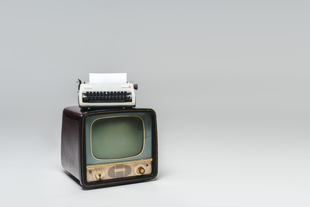 Vintage television with typewriter on top on grey surface
