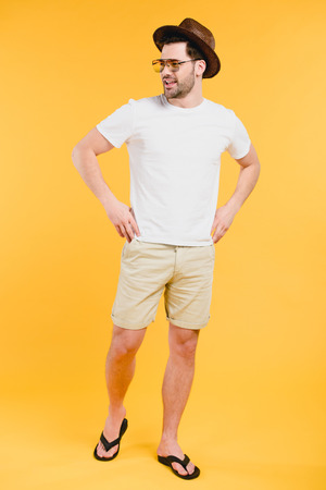 Handsome young man in shorts and flip-flops smiling and looking away isolated on yellow background Stockfoto