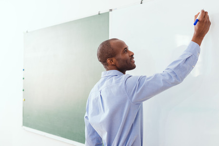 Smiling African American teacher writing on white board in classroom